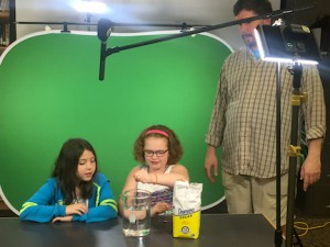 Students Alexis (Sasha) Nielsen, 10, and Landry Mack, 10, at the Bennett Intermediate School practice their lines for a student-produced science video with help from Extension Educator Matt Savatgy.  Courtesy of David Laks, 2017.
