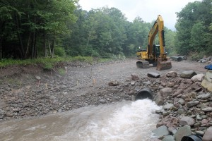 Water is piped through a culvert around the active construction area to help prevent turbidity during construction