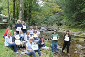 Plein-air painting participants show off their work on the banks of the Esopus.
