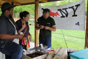 Staff from NYSDEC help prepare a fishing pole for a Family Fun and Fish Day Participant