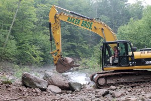 An equipment operator with Baker Brothers Excavating moves a boulder during channel reconstruction.