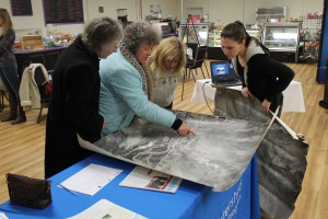 Participants at the 2018 Mappy Hour look over a historical aerial map of the watershed.