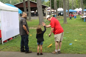 AWSMP/CCEUC Youth Educator Matt Savatgy congratulates a youth who successfully completed the backyard fishing game at Olive Day 2018.