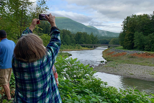 Ashokan Watershed event participan taking a photo of the stream